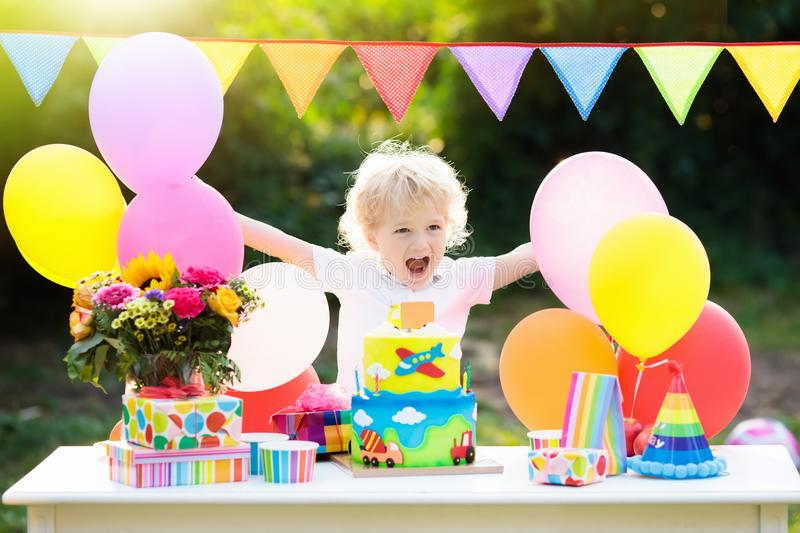Kids birthday party. Child blowing out cake candle. Kids birthday party. Child blowing out candles on colorful cake. Decorated garden with rainbow flag banners stock images