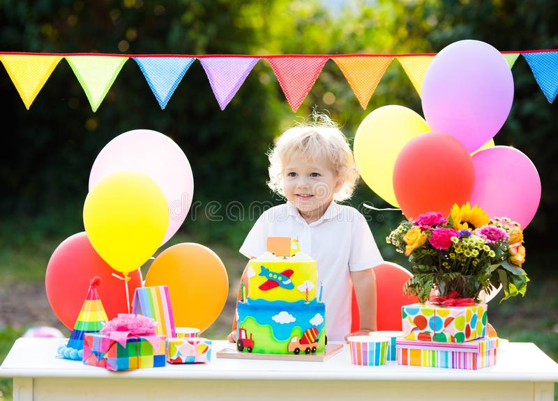 Kids birthday party. Child blowing out cake candle. Kids birthday party. Child blowing out candles on colorful cake. Decorated garden with rainbow flag banners royalty free stock photo