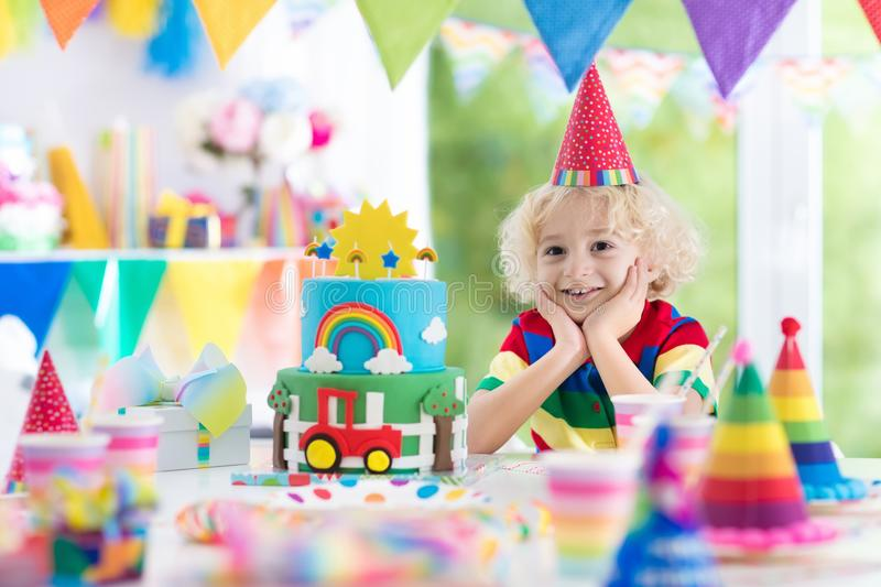 Kids birthday party. Child blowing out cake candle royalty free stock images