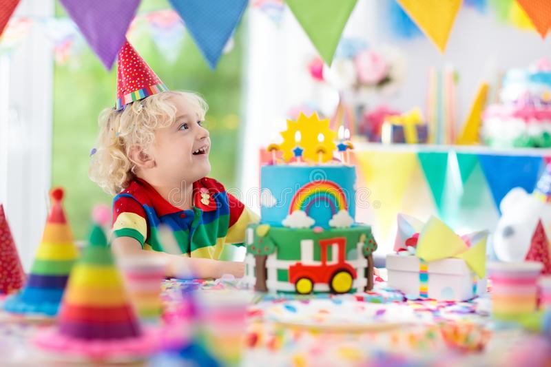 Kids birthday party. Child blowing out cake candle. Kids birthday party. Child blowing out candles on colorful cake. Decorated home with rainbow flag banners royalty free stock photo