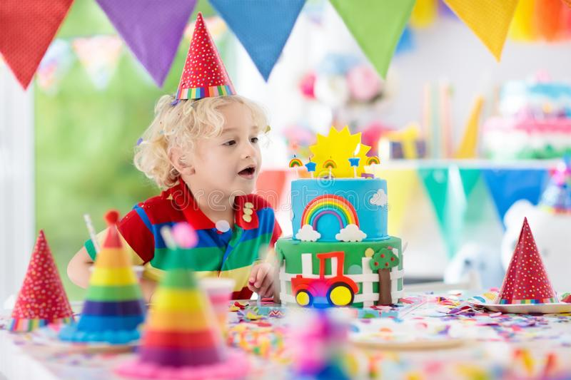 Kids birthday party. Child blowing out cake candle royalty free stock photo