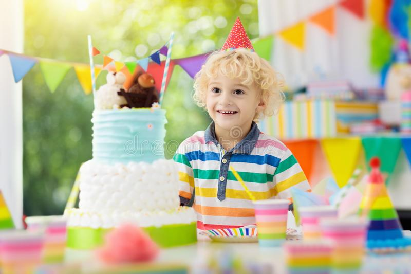 Kids birthday party. Child blowing out cake candle. Kids birthday party. Child blowing out candles on colorful cake. Decorated home with rainbow flag banners royalty free stock image