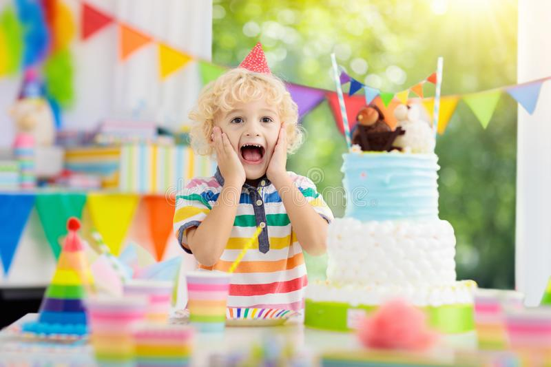 Kids birthday party. Child blowing out cake candle. Kids birthday party. Child blowing out candles on colorful cake. Decorated home with rainbow flag banners royalty free stock images