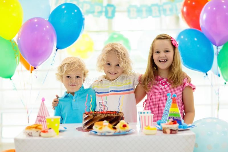 Kids birthday party. Child blowing out candles on colorful cake. Decorated home with rainbow flag banners, balloons. Farm animals royalty free stock photography