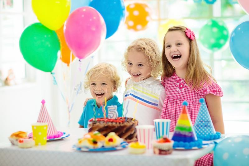 Kids birthday party. Child blowing out candles on colorful cake. Decorated home with rainbow flag banners, balloons. Farm animals. Theme celebration. Little boy stock images