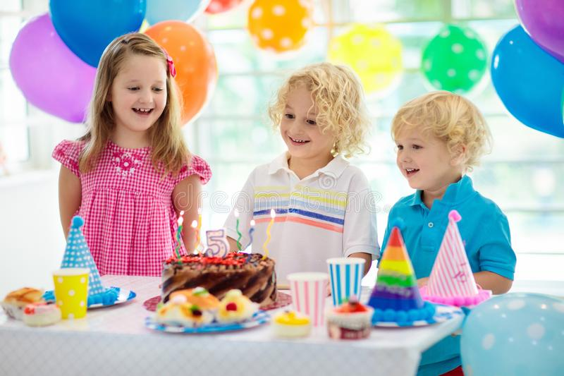 Kids birthday party. Child blowing out candles on colorful cake. Decorated home with rainbow flag banners, balloons. Farm animals stock photo