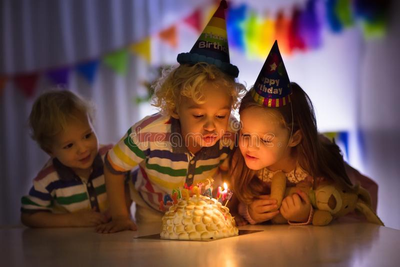 Kids birthday party. Children blow cake candles. Kids birthday party. Children blow out candles on cake in dark room. Rainbow decoration and table setting for royalty free stock photos