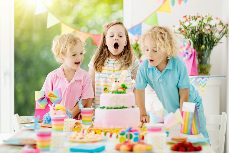 Kids birthday party. Children blow cake candles. Kids birthday party. Children blow out candles on pink bunny cake. Pastel rainbow decoration and table setting royalty free stock image