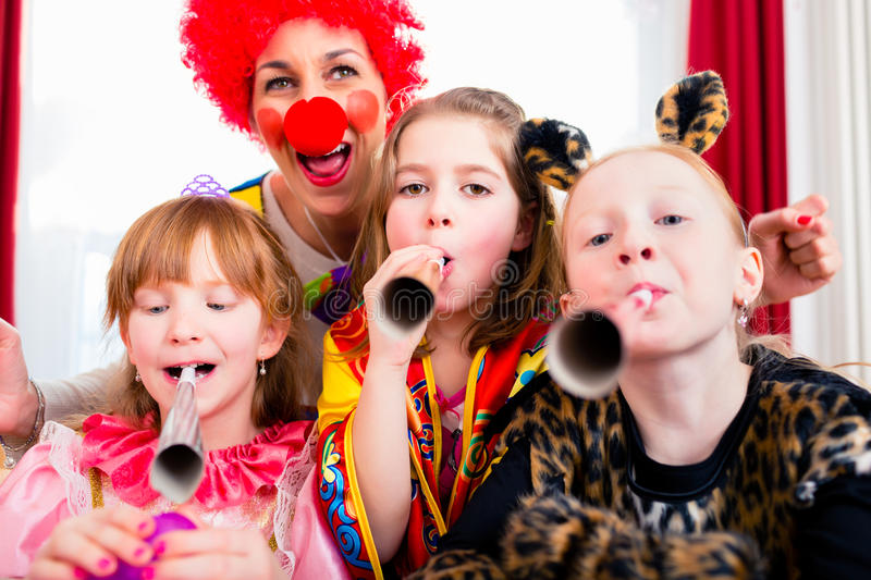 Kids birthday party with clown and lot of noise. Children celebrating birthday party with noisemakers while a clown is visiting entertaining the kids royalty free stock photo