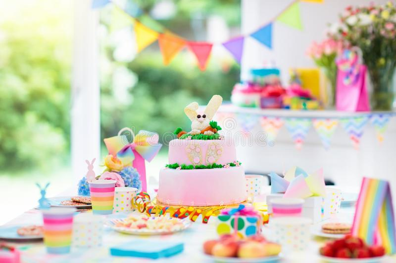Kids birthday party decoration and cake. Decorated table for child birthday celebration. Rainbow bunny cake for little girl. Room with festive balloons stock photography