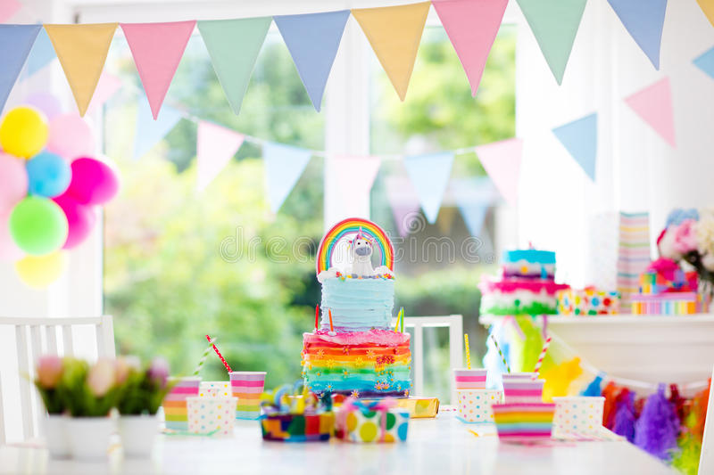 Kids birthday party decoration and cake. Decorated table for child birthday celebration. Rainbow unicorn cake for little girl. Room with festive balloons stock image