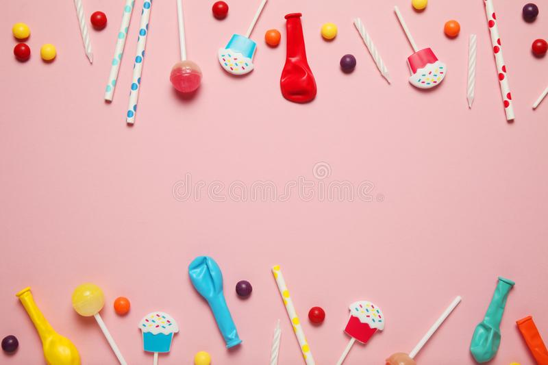 Kids birthday party decoration, pink background pattern. Colorful candies, bright balloon, festive candles, and paper straws stock photo
