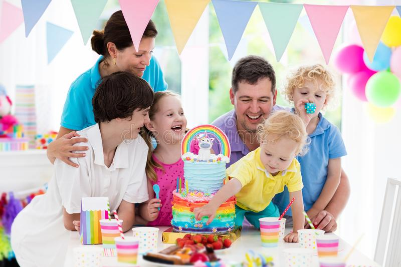 Kids birthday party. Family celebration with cake. Kids birthday party with unicorn rainbow cake for little girl. Family celebrating child birthday. Parents and royalty free stock photography