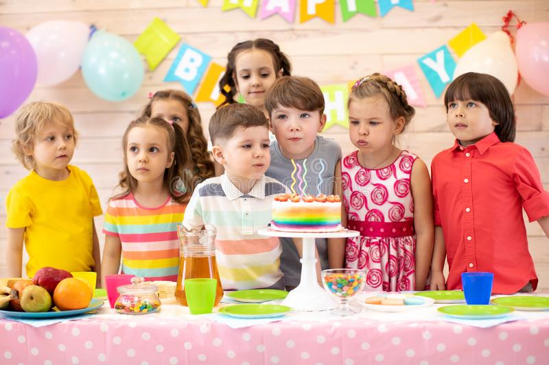 Kids birthday party. Group of adorable preschoolers looking at birthday cake. Children blowing on candles stock images