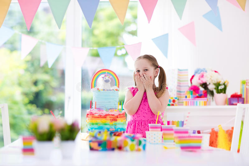 Kids birthday party. Little girl with cake. Kids birthday party with colorful pastel decoration and unicorn rainbow cake. Little girl with sweets, candy and royalty free stock photo