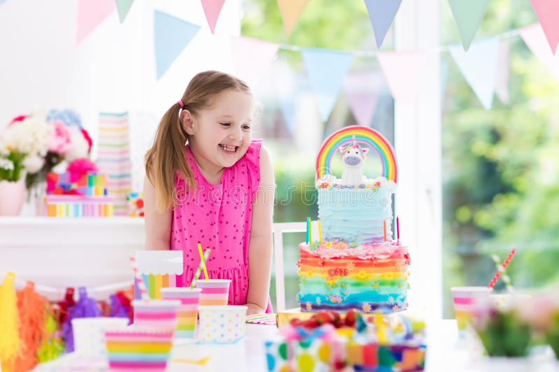 Kids birthday party. Little girl with cake. Kids birthday party with colorful pastel decoration and unicorn rainbow cake. Little girl with sweets, candy and stock photography