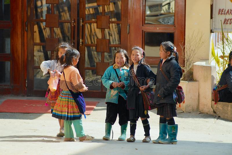 Kids of the Black Miao Hmong minority hill tribe wearing traditional costumes talk at the street in Sapa, Vietnam. royalty free stock photos