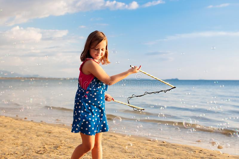 Kids blow bubble at beach. Child with bubbles stock photo