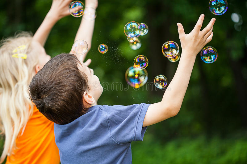 Kids blowing bubbles. Two kids having fun blowing bubbles in the park stock images