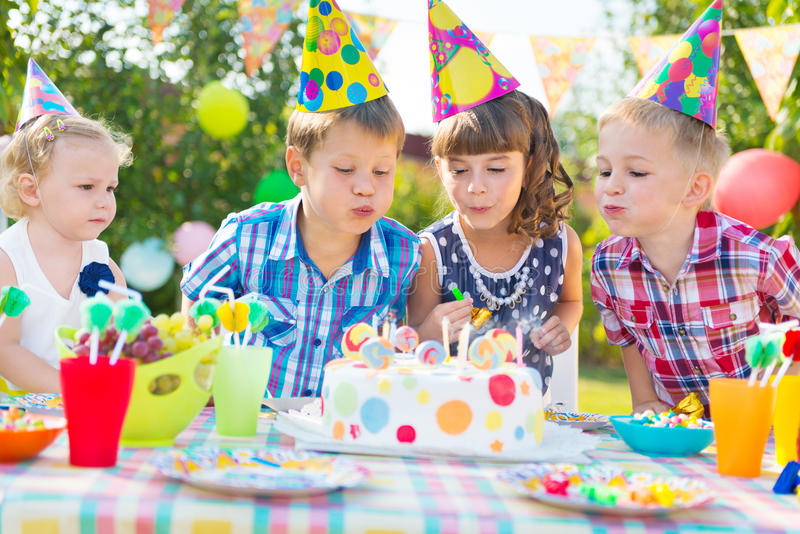 Kids blowing candles on cake at birthday party. Kids celebrating birthday party and blowing candles on cake royalty free stock image
