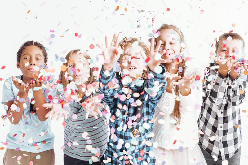 Kids blowing confetti. Group of joyful kids merrily blowing colorful confetti into the air royalty free stock photos
