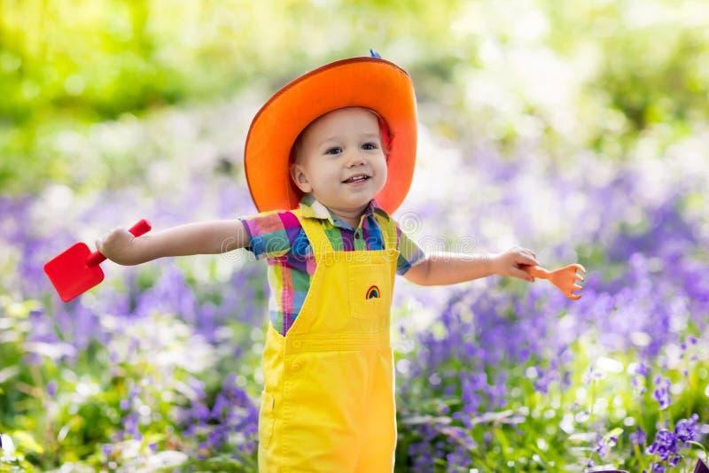 Kids in bluebell garden. Kids in bluebell woodland. Child with flowers, garden tools and wheelbarrow. Boy gardening. Children play outdoor in bluebells, work royalty free stock image