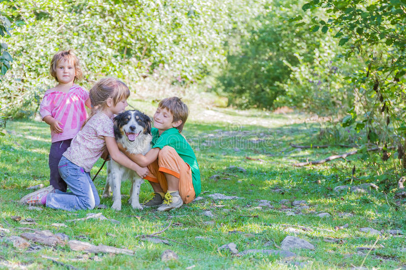 Kids - boy and girl - with dog outdoors. Three kids - boy and girls - with dog outdoors royalty free stock photos