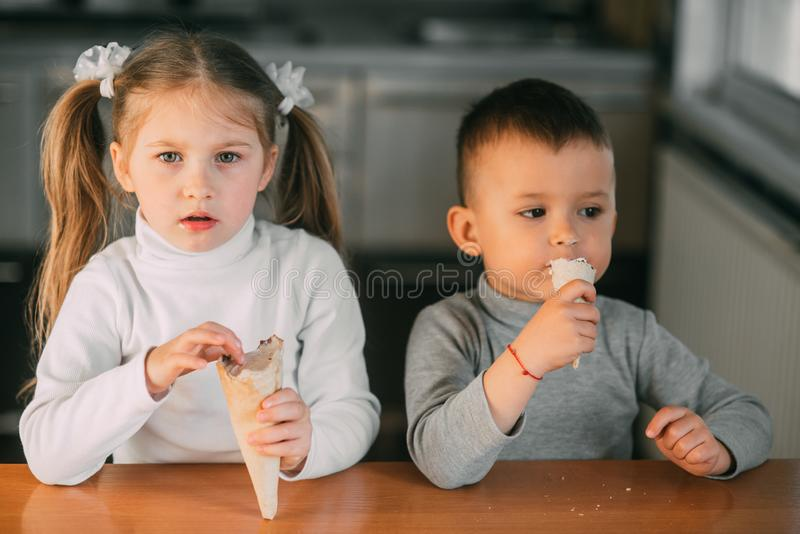 Kids boy and girl eating ice cream cone in the kitchen is a lot of fun royalty free stock photo