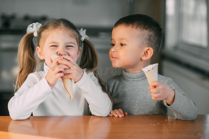 Kids boy and girl eating ice cream cone in the kitchen is a lot of fun stock photo