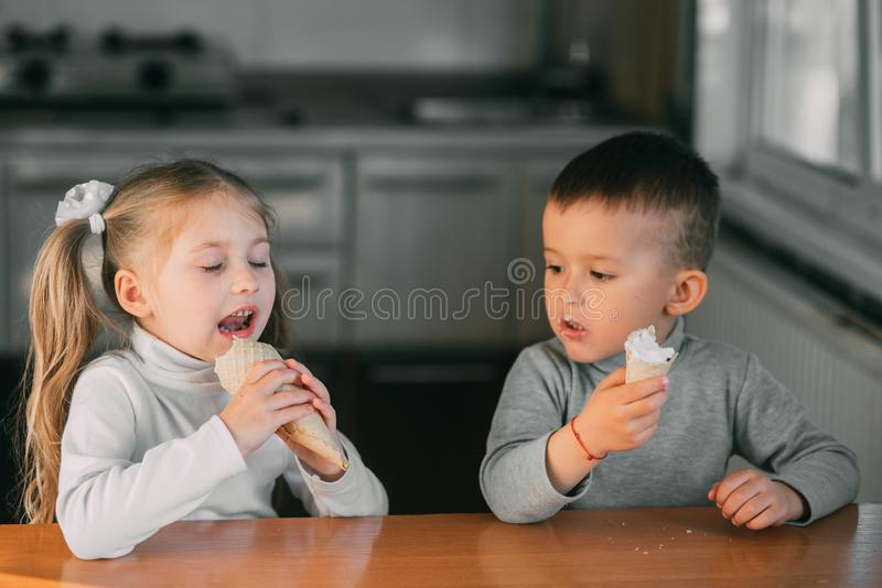 Kids boy and girl eating ice cream cone in the kitchen is a lot of fun stock photography