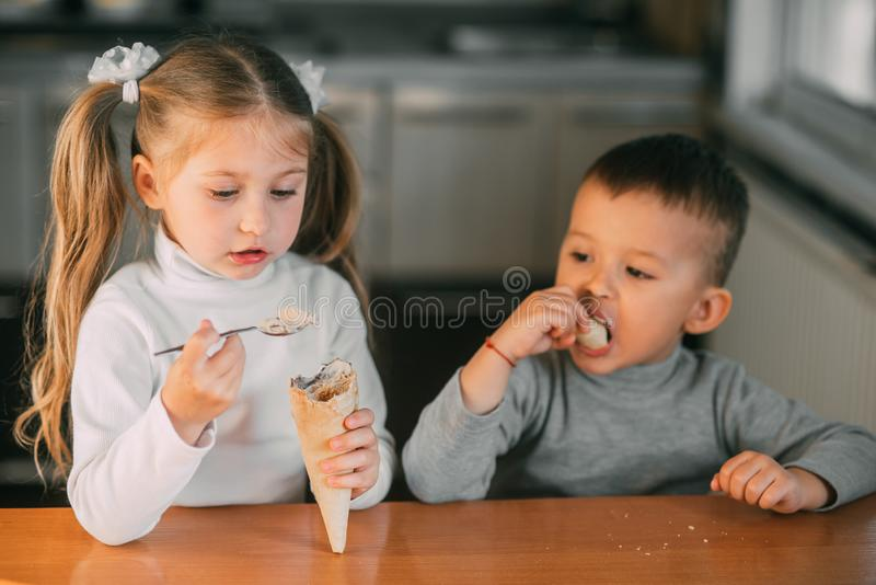 Kids boy and girl eating ice cream cone in the kitchen is a lot of fun stock images