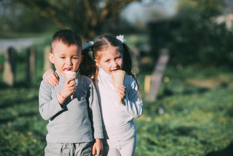 Kids Boy and girl eating ice cream outdoors on grass and trees background stock images
