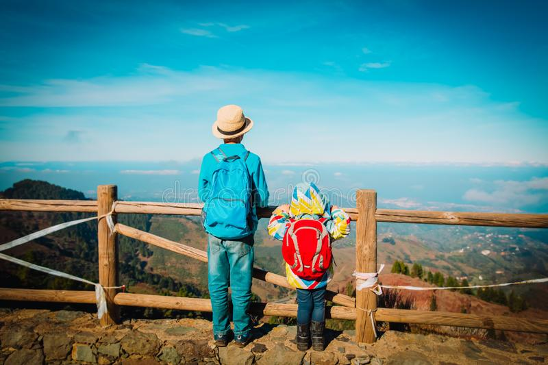 Kids - boy and girl -looking at scenic view while travel in mountains royalty free stock image