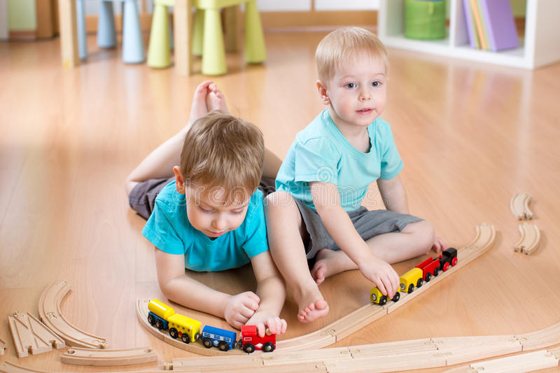Kids boys play with railroad and trains indoor, learning and daycare royalty free stock image