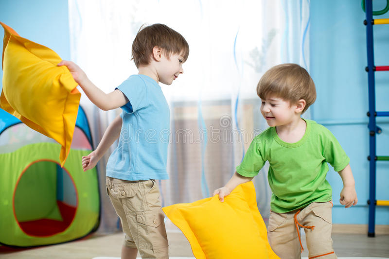 Kids boys playing with pillows stock images