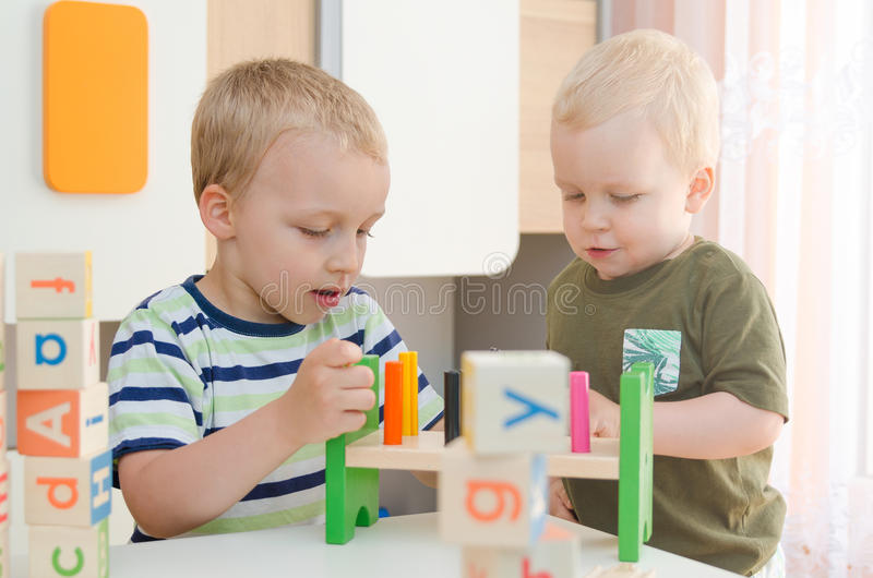 Kids boys playing with toy blocks at home or kindergarten stock photos