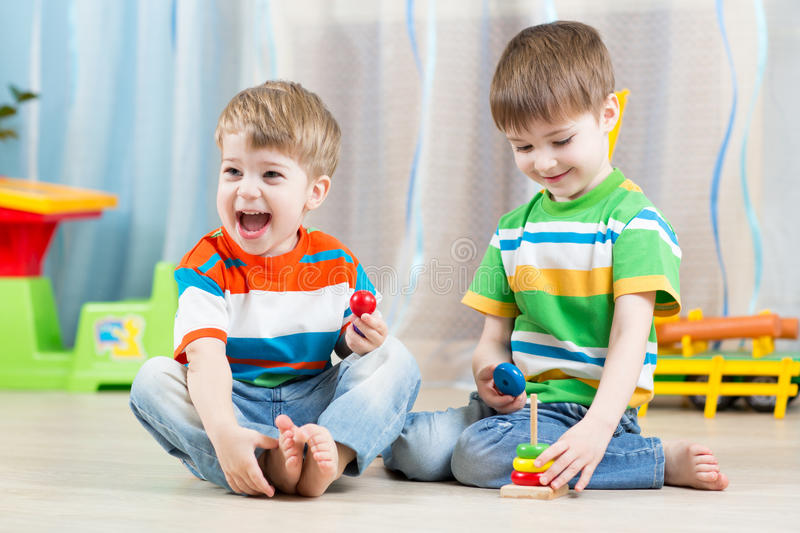 Kids boys with toys in playroom. Kids boys with educational toy in playroom stock photo