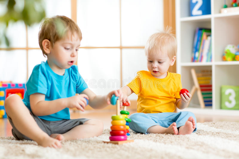Kids boys with toys in playroom. Kids boys with educational toy in playroom royalty free stock photo