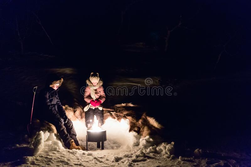 Kids outdoors on winter. Kids brother and sister by a campfire in winter forest at night royalty free stock photos