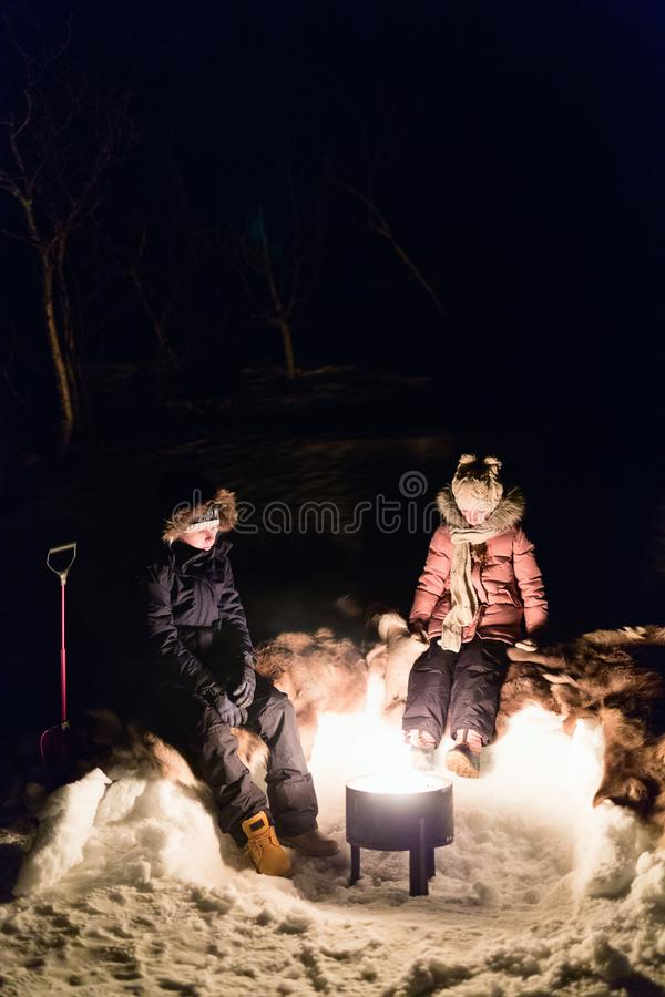 Kids outdoors on winter. Kids brother and sister by a campfire in winter forest at night royalty free stock image