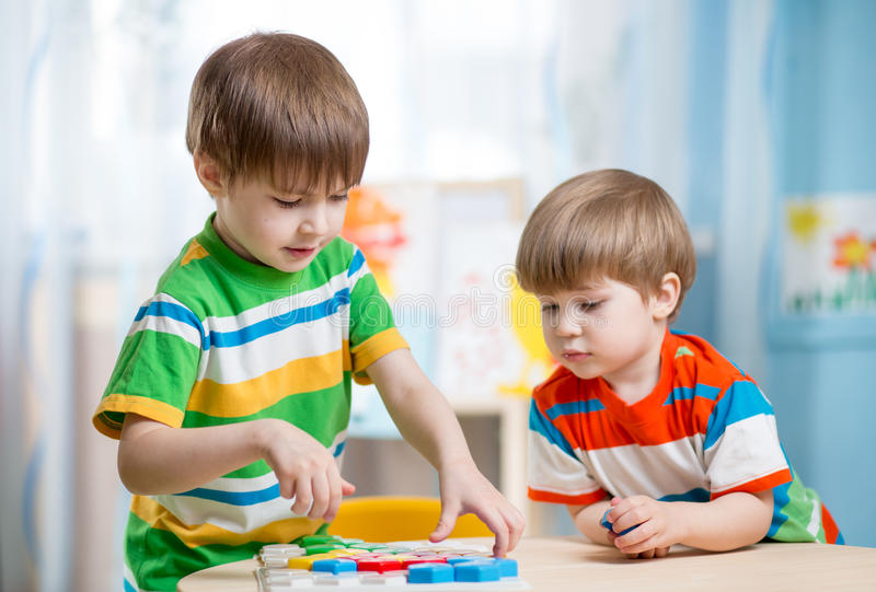 Put Together Toys For Boys : Kids brothers playing together at table stock photo