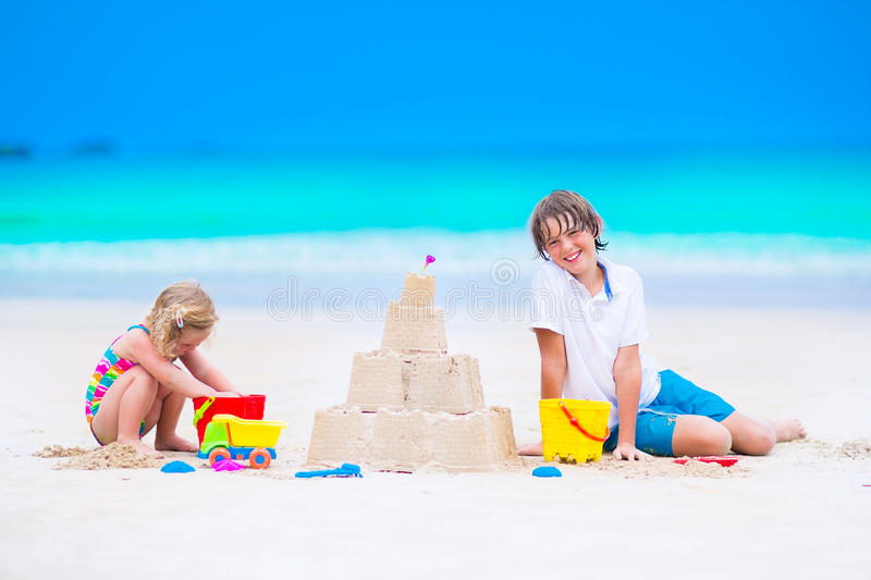 Kids building sand castle on the beach stock photography