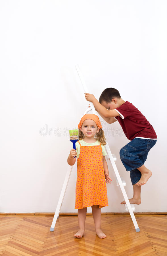Kids busy preparing to paint the wall royalty free stock photography