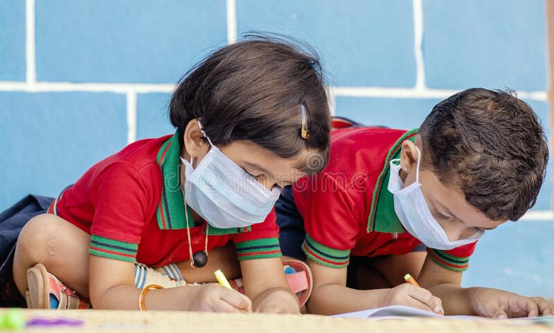 Kids busy in writing with medical face mask wearing due to covid-19 or coronavirus outbreak or pandemic at school -. Kids busy in writing with medical face mask stock photo