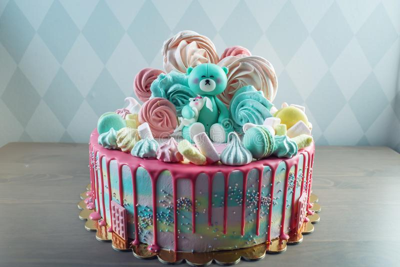 Kids cake decorated with Teddy bear and colorful meringues, marshmallows. Concept of desserts for the birthday children royalty free stock photos