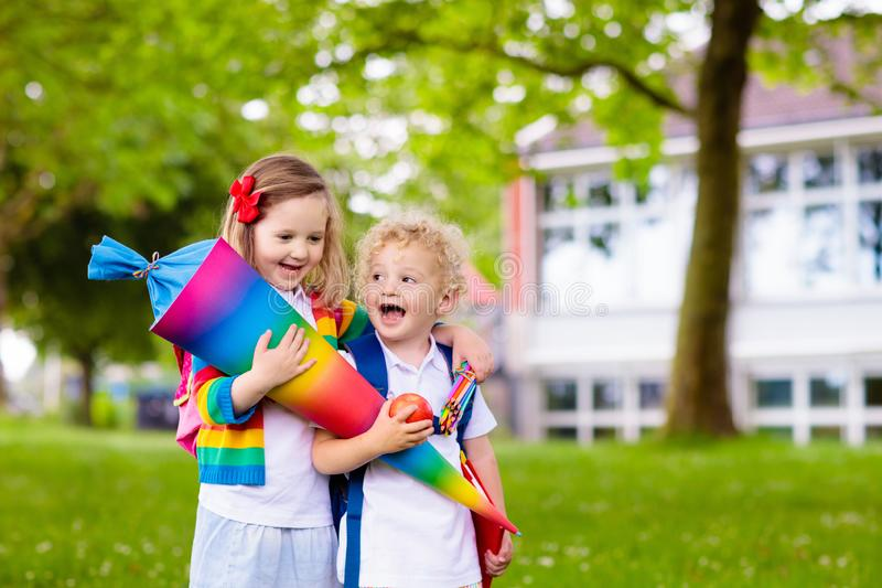 Kids with candy cone on first school day in Germany. Child going to school. Boy and girl holding traditional candy cone on the first school day. Little students royalty free stock photography