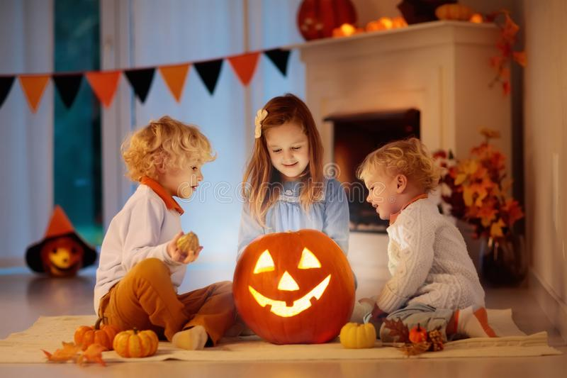 Kids carving pumpkin on Halloween. Trick or treat. Kids carving pumpkin on Halloween at home sitting next to fireplace in living room decorated with lanterns stock photography