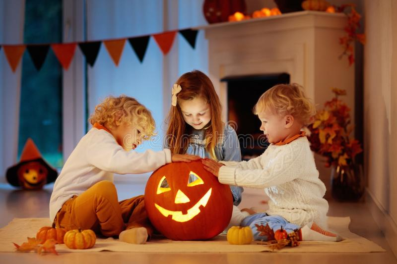 Kids carving pumpkin on Halloween. Trick or treat. Kids carving pumpkin on Halloween at home sitting next to fireplace in living room decorated with lanterns royalty free stock image
