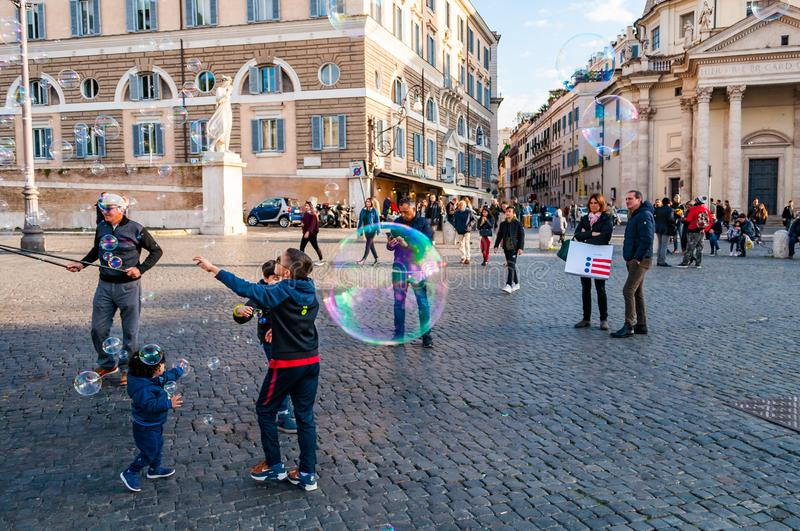 Kids catching and blowing soap bubbles flying on Piazza del Popolo, People Square in Rome full of people, tourists and locals with stock photo