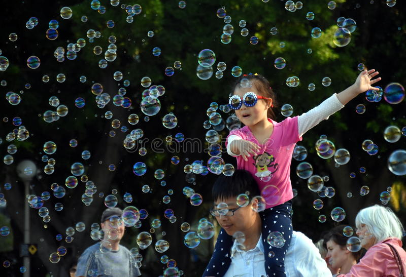 Kids catching and having fun and with soap bubbles stock photography